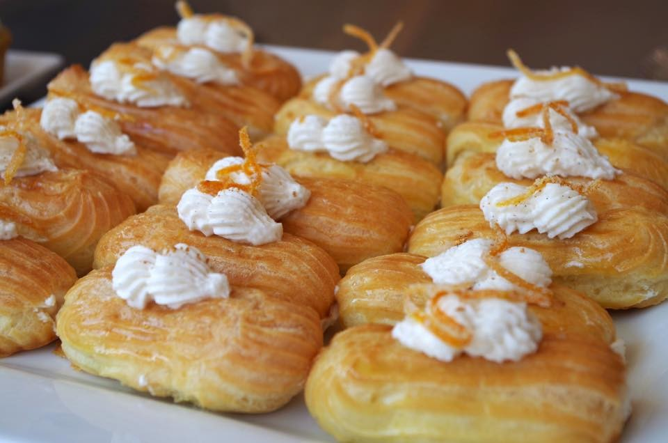 Rows of golden puff pastries topped with cream and candied orange peel, from OCD Cakes.