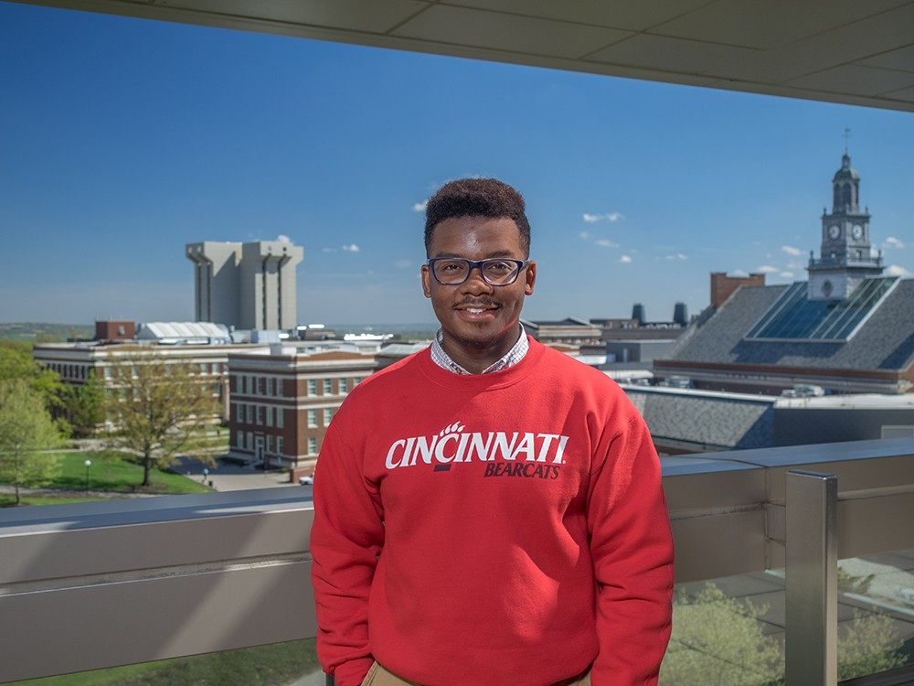 James Avant IV poses for a photo on UC's campus in a red Bearcats sweatshirt