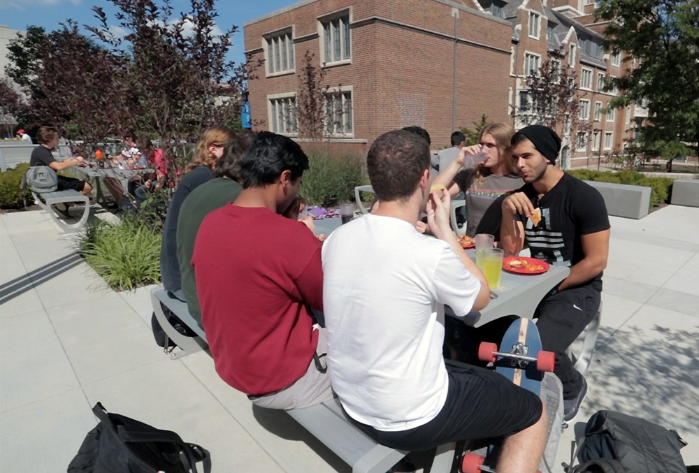 UC students sit at a table and eat food on campus