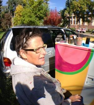 Amelia Caruso paints a transformer box in Fort Collins, Colo.