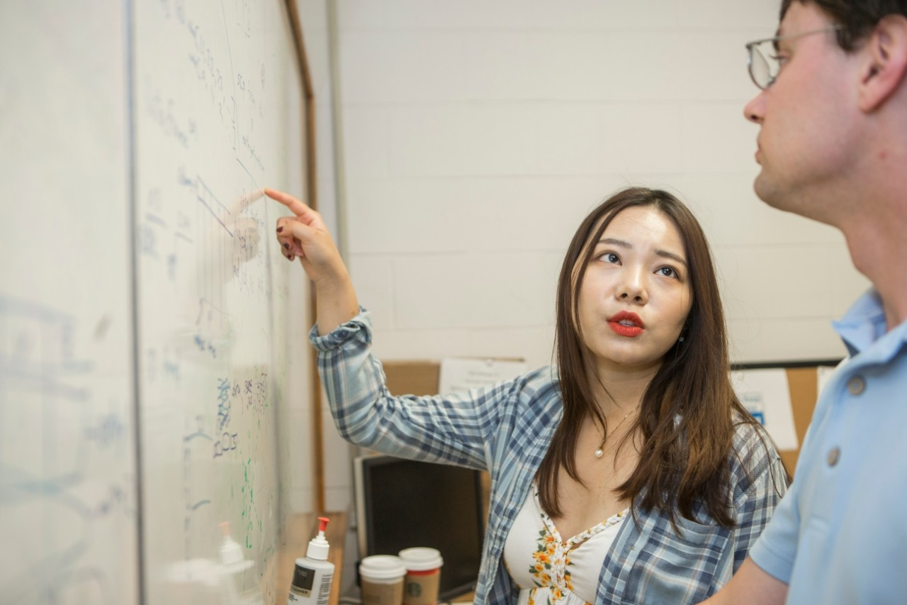 Chongqing University student Yixuan Zhang talks about an equation with her advisor while working on a research project at UC this summer. She will earn degrees from both universities this year.