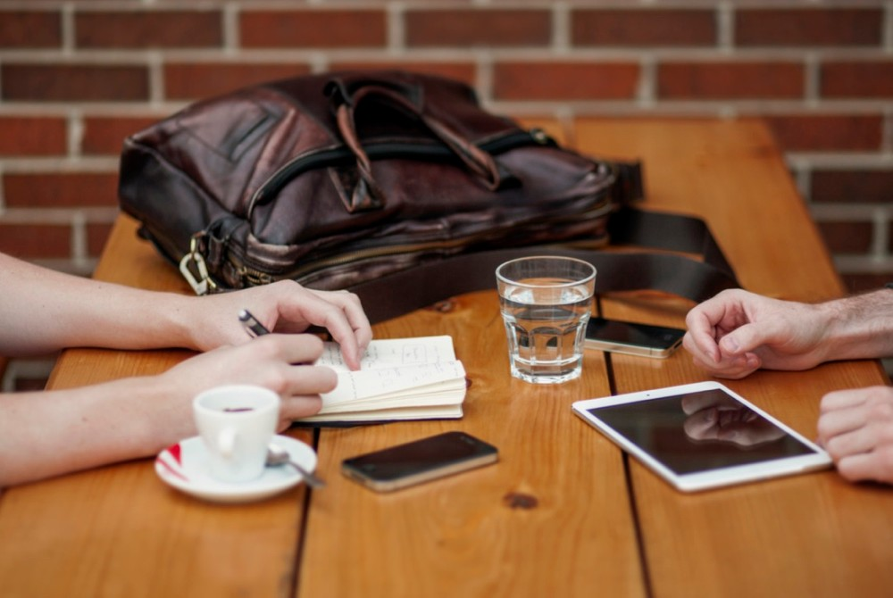 Table in a coffee shop holding a backpack, ipad tablet, smartphone and beverages. photo/Flickr Commons