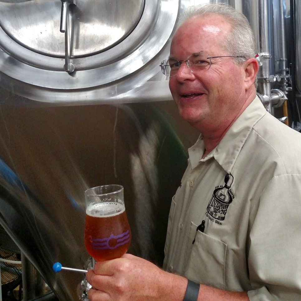 Allen Moellman, pilot brewer for Listerman's Brewery, holds a fresh glass of craft beer.