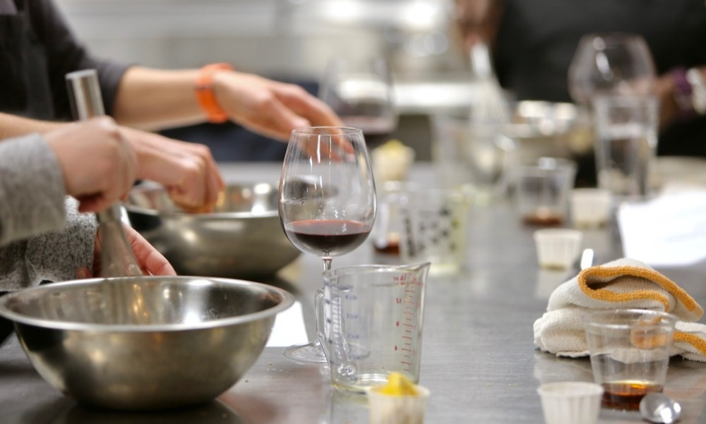 Bowls, glasses and hands stir and create vinaigrette dressing at a cooking class.