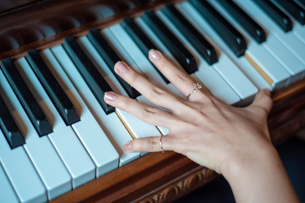 A woman's hand over piano keys.