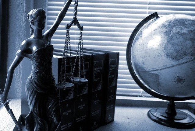 Bronze statue of Lady Justice holding balance scales sits before a cluster of books and a world globe on a table.