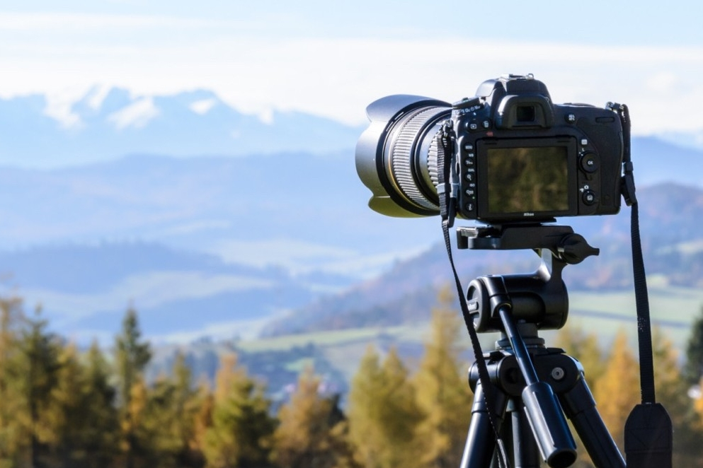 Back of a DSLR camera and lens points to a mountain range.