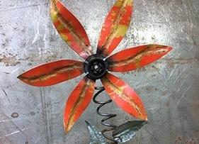 A welded orange metal flower.