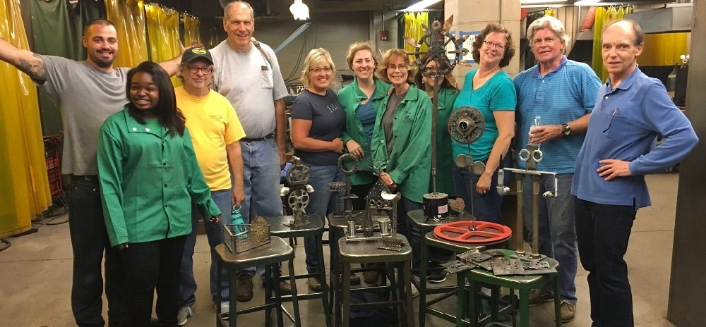 Students in a UC Communiversity welding class stand together displaying their welded objects.