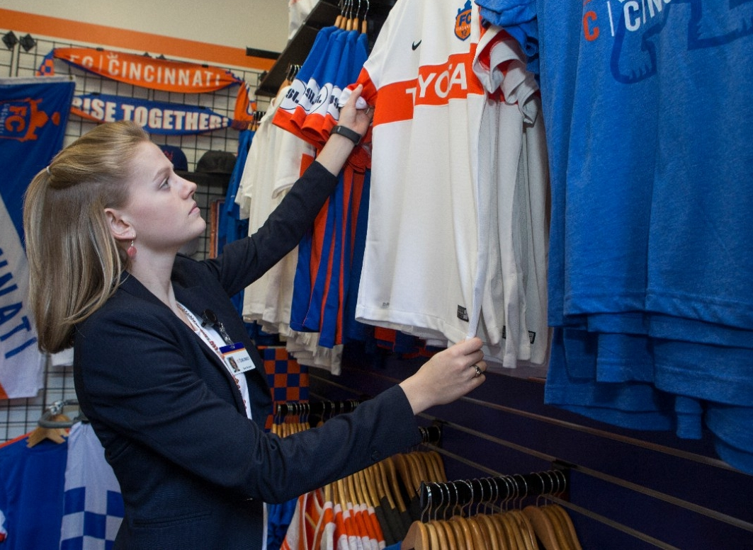 UC student Samantha Burgess arranges some promotional jerseys in the store at FC Cincinnati.