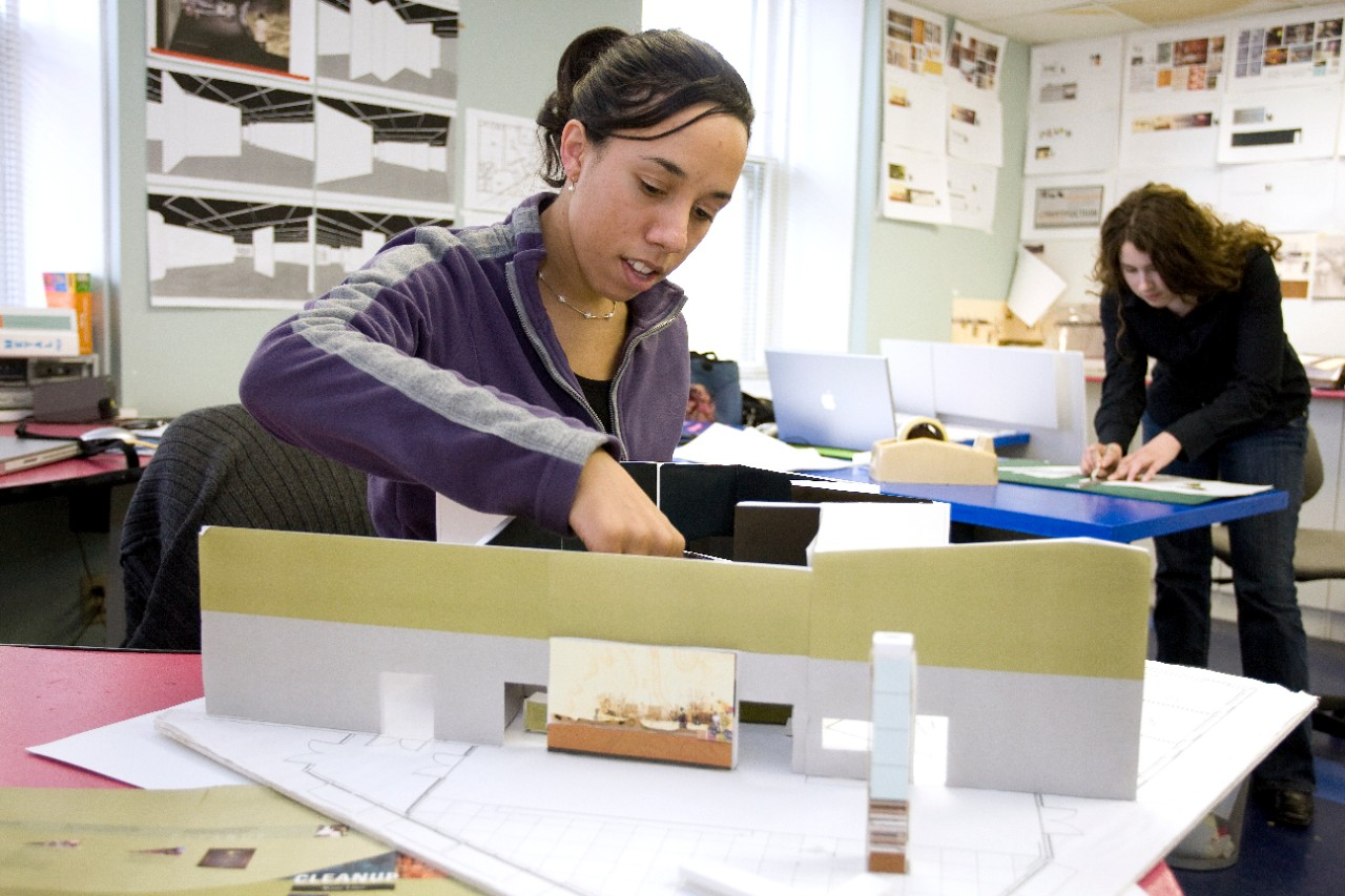 A UC co-op student works on a diorama for her employer.