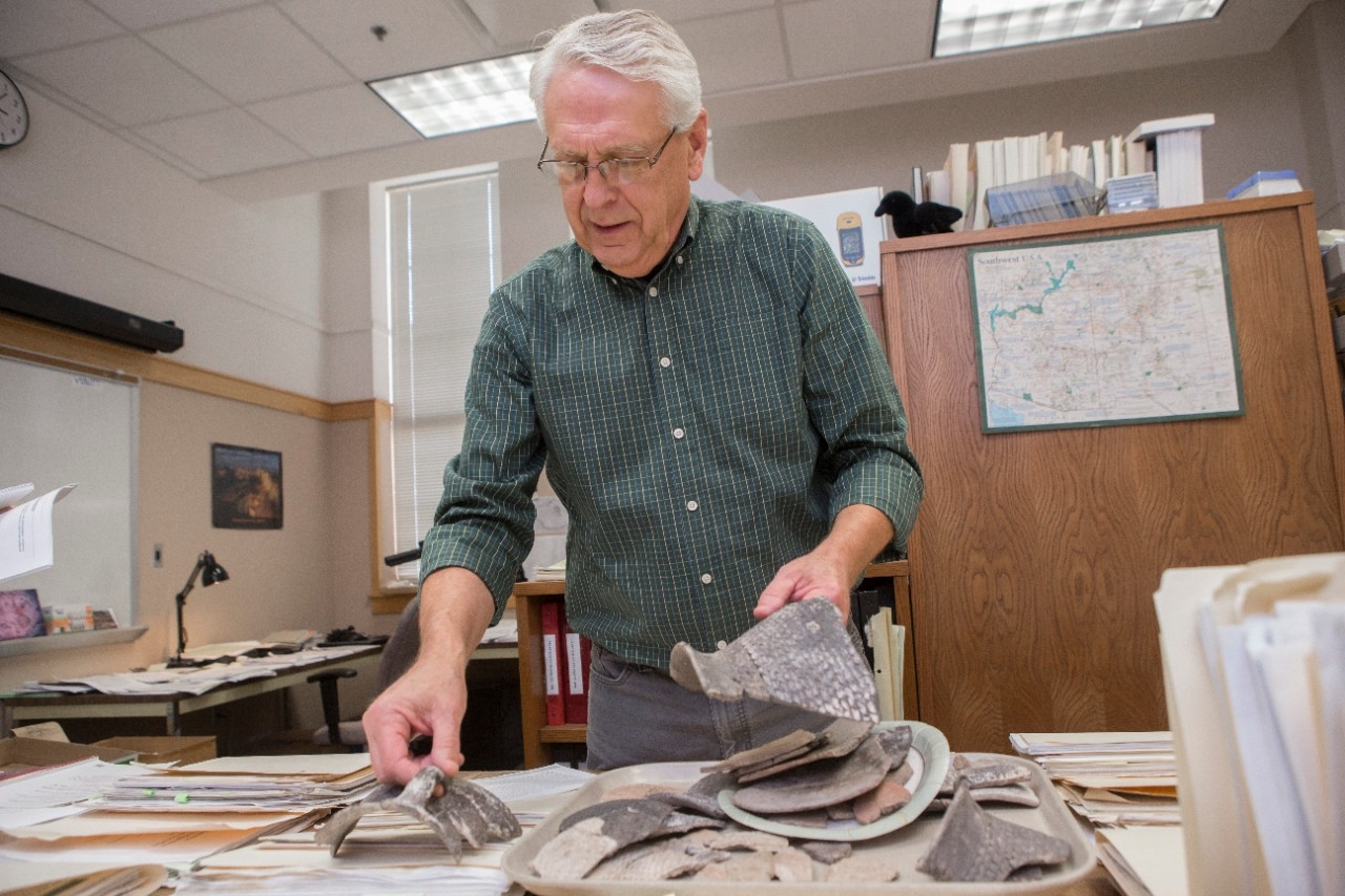 UC archaeologist Alan Sullivan holds prehistoric pottery found at sites outside Arizona's Grand Canyon National Park.