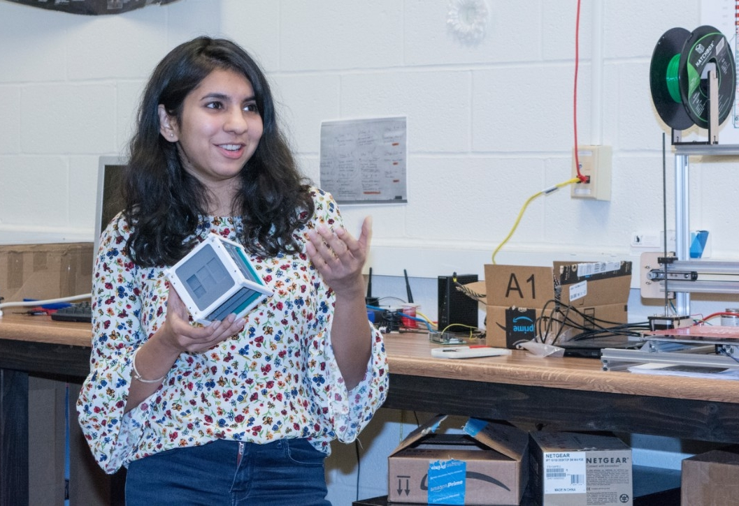 UC CubeCats President Himadri Pandey holds a model of a cubesat in the club's lab.
