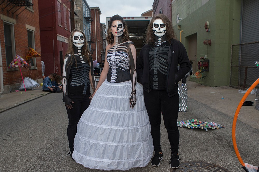 Three BLINK parade participants pose in skeleton costumes.