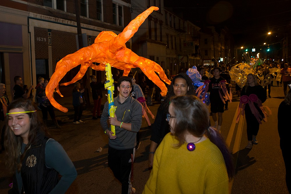 DAAP students display illuminated Body Mantle projects made from inexpensive materials and light-up components. A large orange octopus sculpture is being carried.
