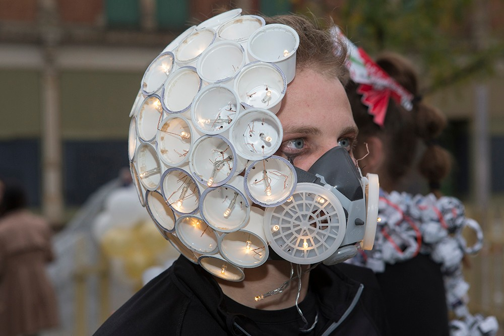 DAAP students display illuminated Body Mantle projects made from inexpensive materials and light-up components. Here, one man wears a headpiece made of disposable plastic cups.
