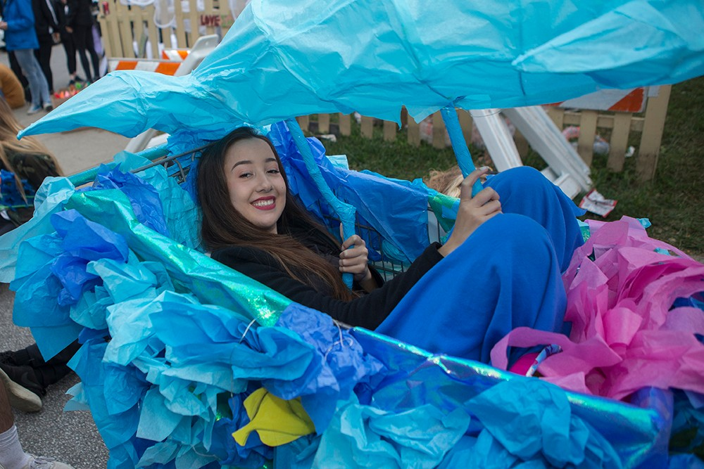 A woman sits in a car decorated with blue tissue paper in the BLINK parade.