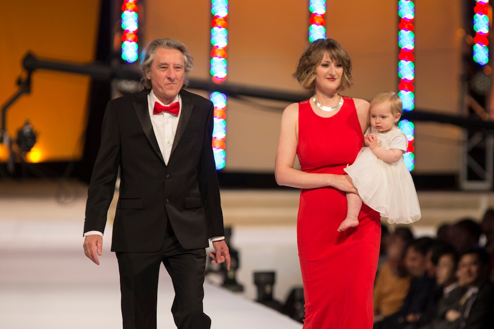 A man in a black suit with red bowtie walks a runway with a woman in a red dress and a baby in a white dress.