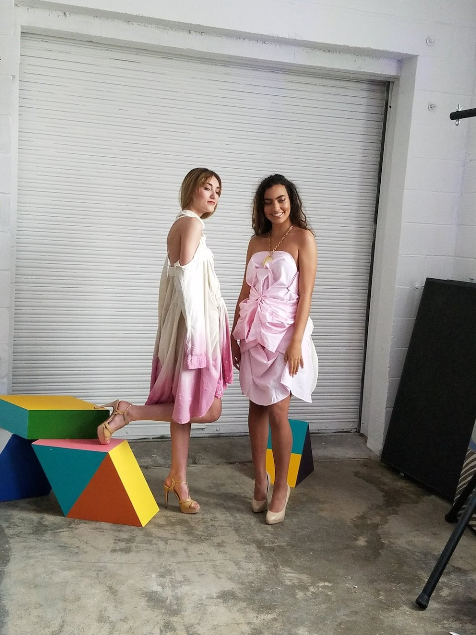 Two models wear pink dresses made from white button-up shirts