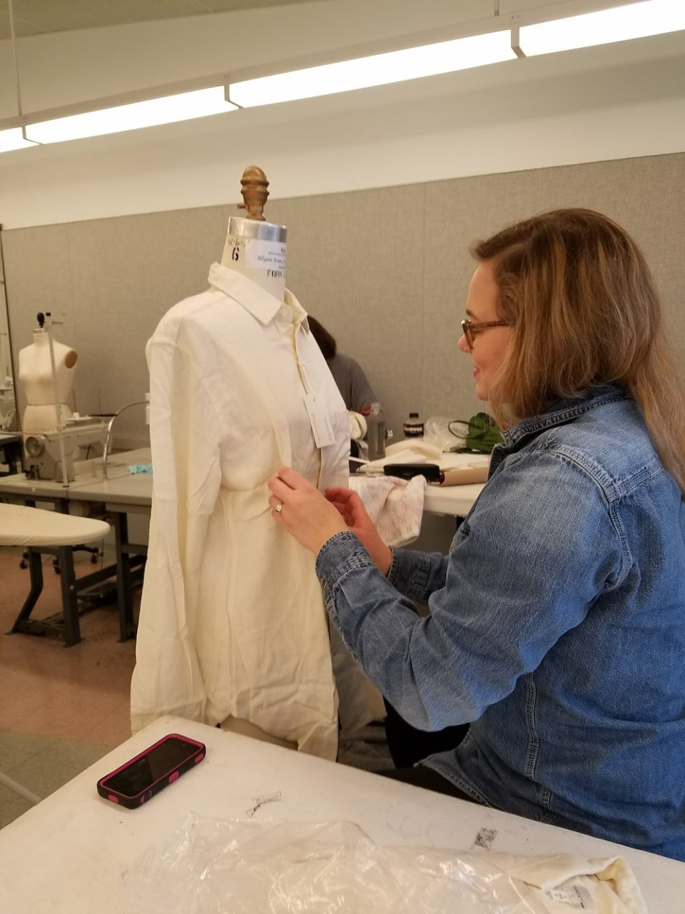 A student fits a garment made from two white button-up shirts on a dress form.