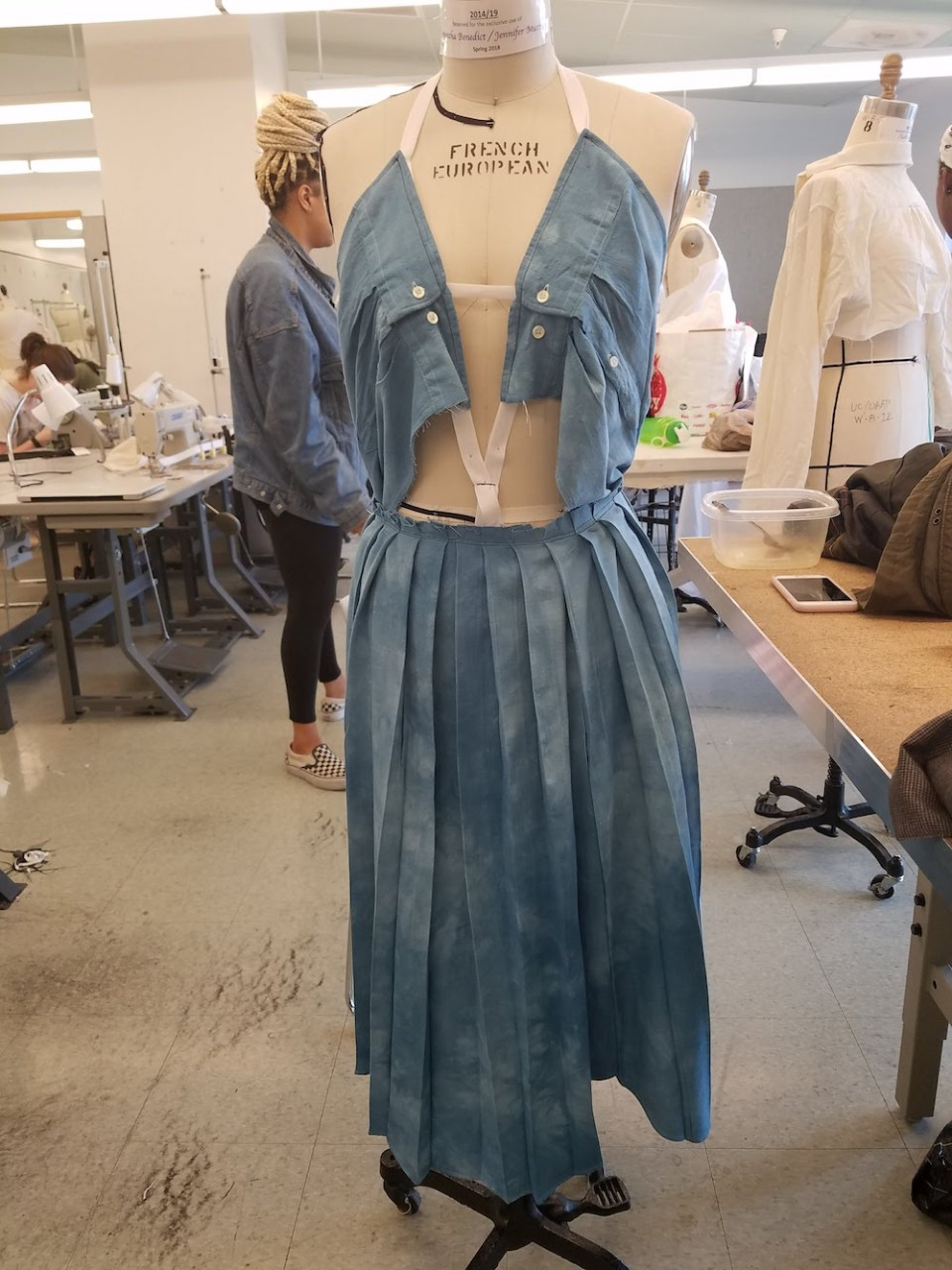A blue dress made from two white button-up shirts on a dress form.