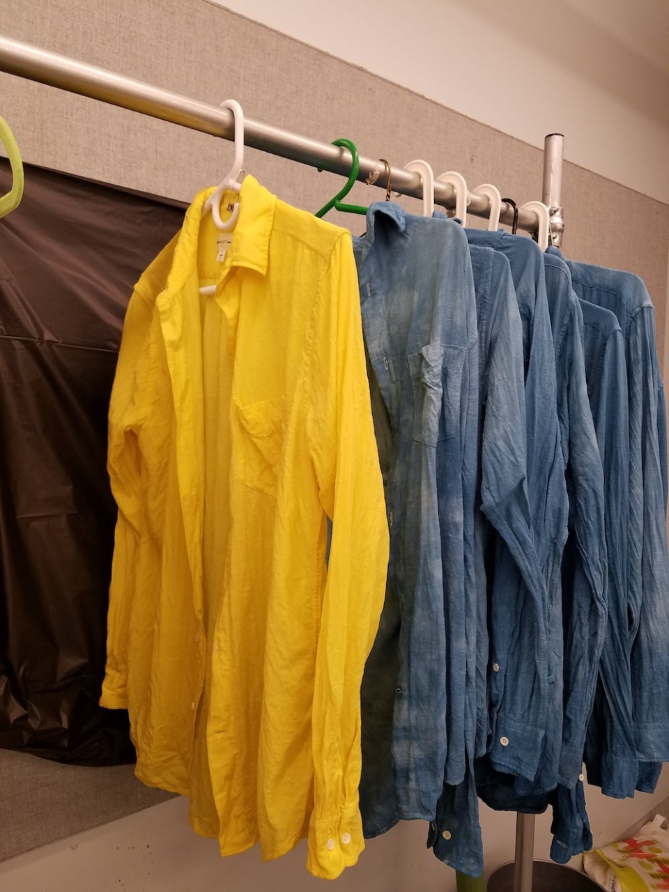 White button-up shirts dyed yellow and blue hang on a clothing rack.