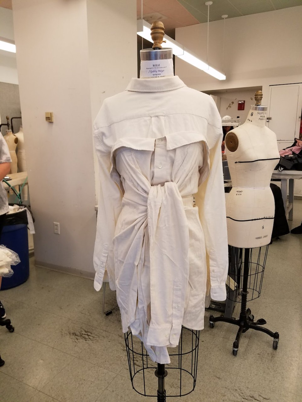 A garment made from two white button-up shirts on a dress form