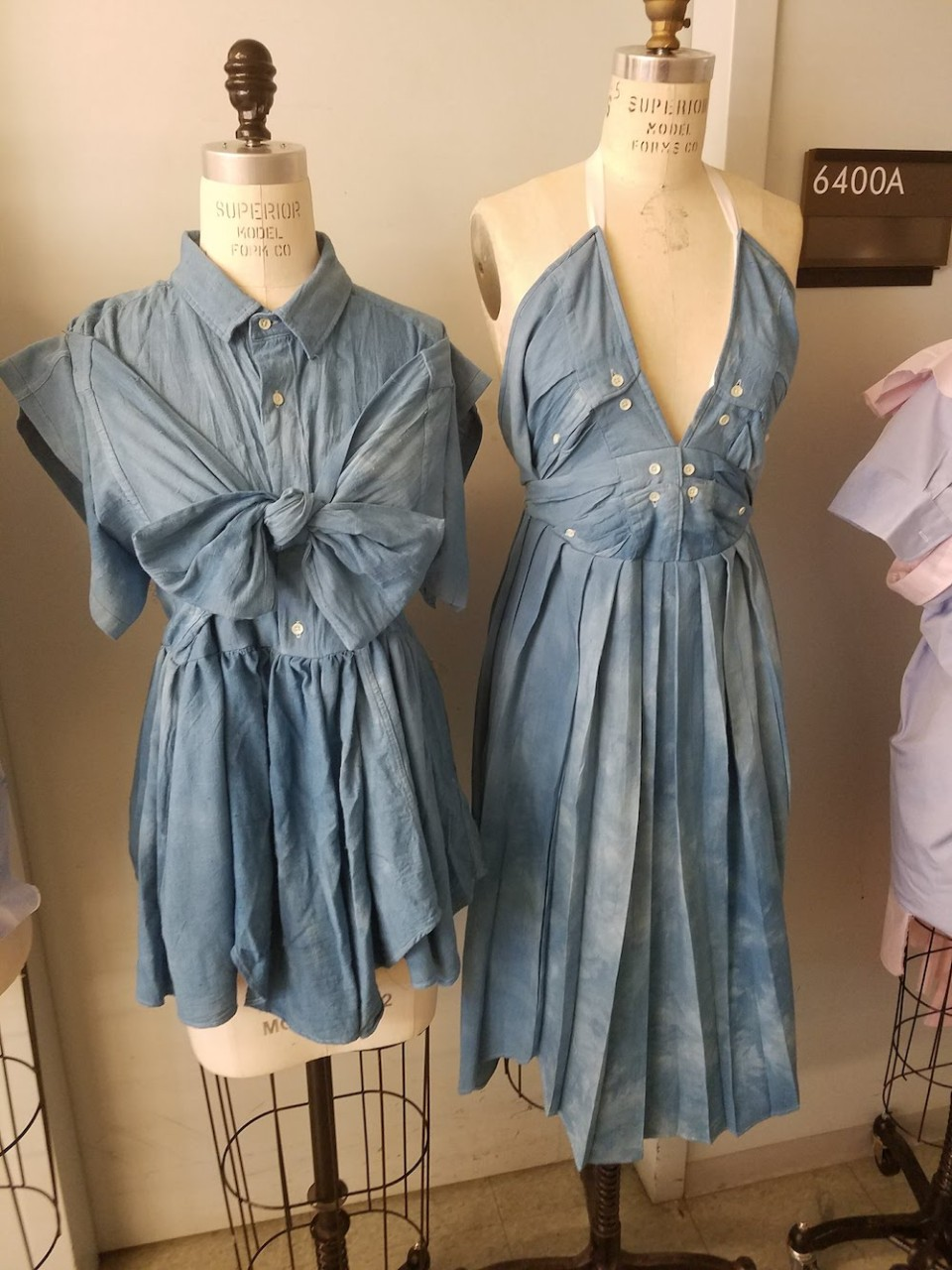 Two blue dresses made from two white button-up shirts on a dress form.