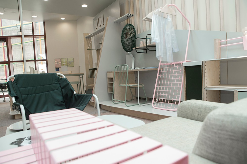 Another angle of the furniture display, with a black vinyl shair, pink magazine rack, light wood desk with a pale green chair.