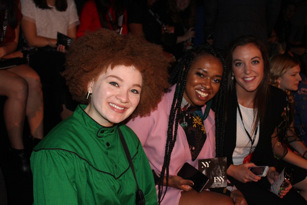 Julia Bond, Asha Ama Daniels-Henderson and Meredith Kussmaul sit in a row to watch a NYFW runway show.