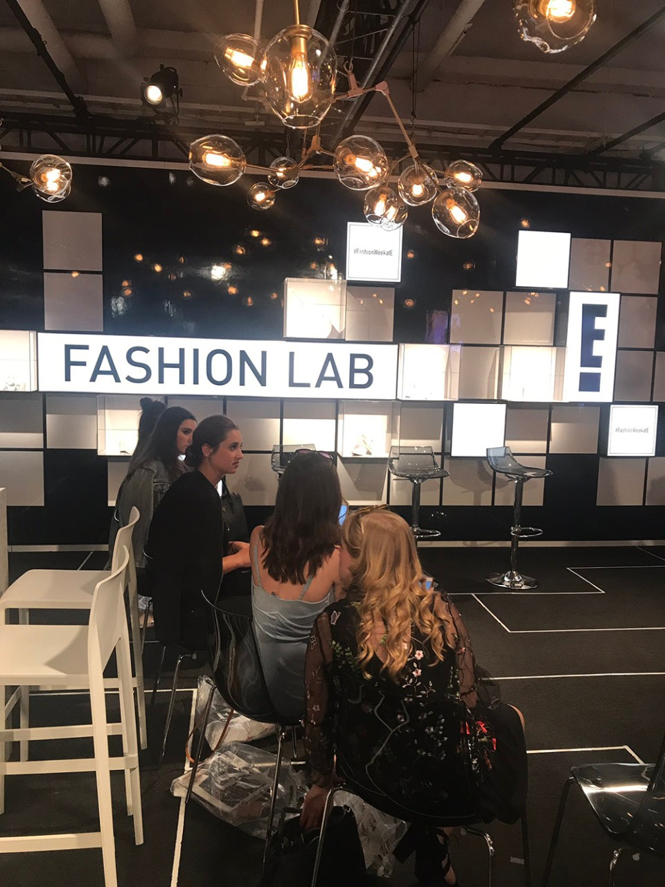 A shot of the E! Fashion Lab, decorated with round lamps and white light-up squares on the wall. This is where the entertainment network covers all things fashion week.