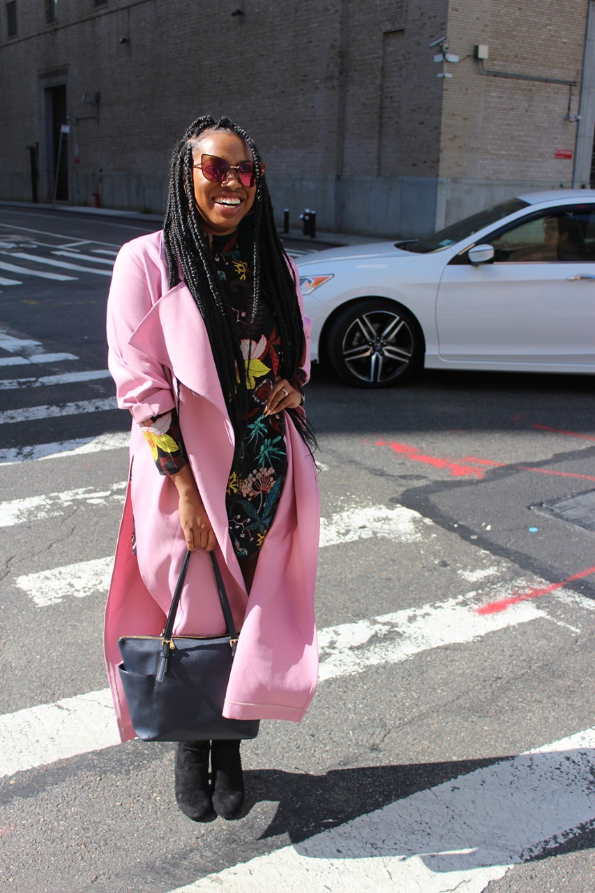 Asha Ama Daniels wears a pink trench coat she design and made as she poses in a New York street.