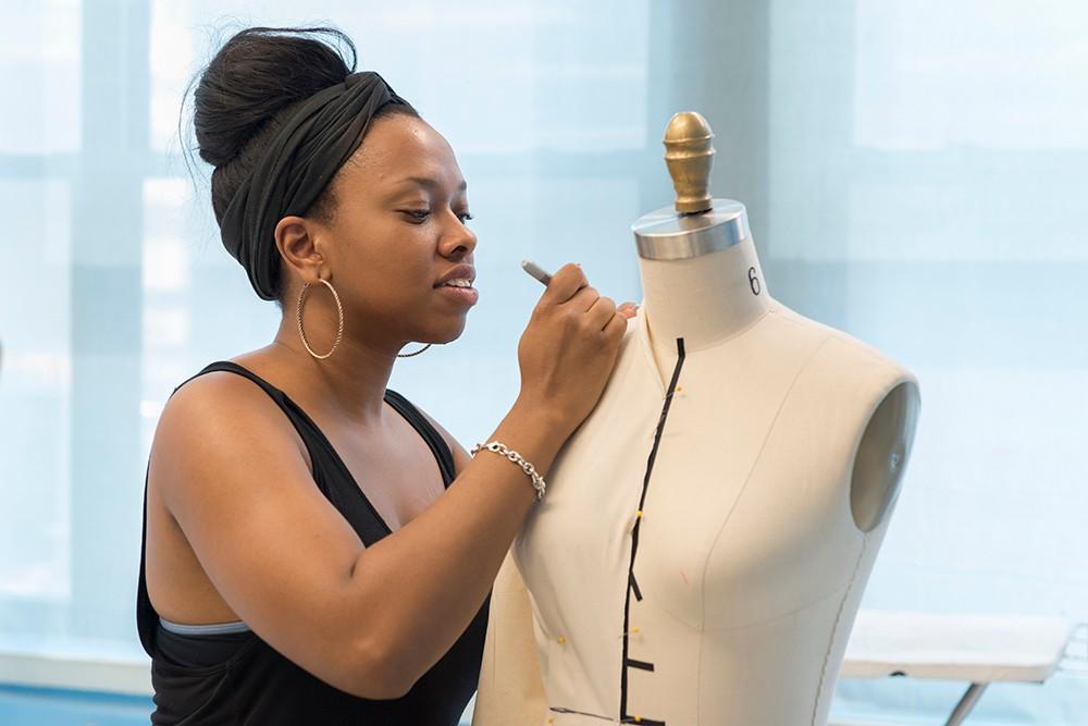 Asha Ama Daniels-Henderson fits fabric on a dress form on Project Runway All Stars.