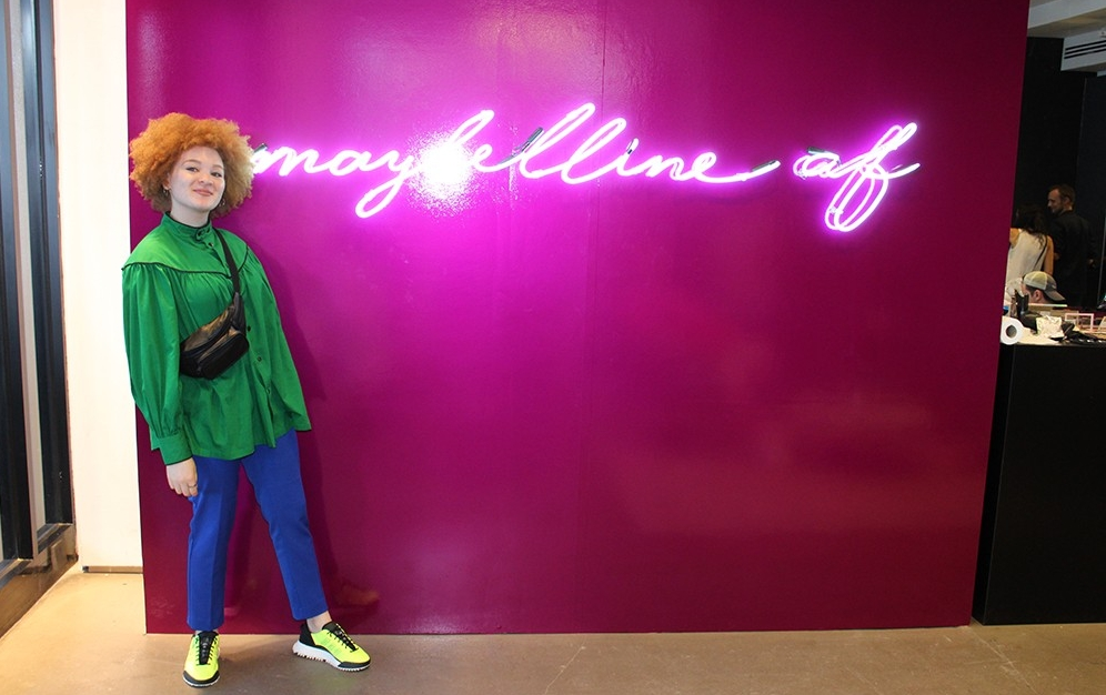 Julia Bond wears a green blouse and blue pants as she poses in front of a bright pink wall at the NYFW Maybelline pop-up event.