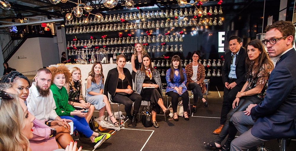 Design students from across the country, including UC, talk shop with industry professionals at New York Fashion Week. Students sit in a half-circle across from three IMG fashion executives in the E! Fashion Lab.