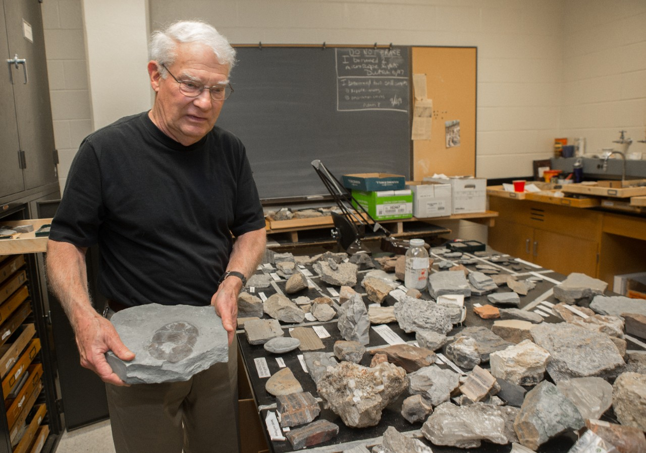 UC geology professor emeritus David Meyer holds a trilobite fossil in a UC geology lab full of specimens, some donated by the Cincinnati Dry Dredgers.