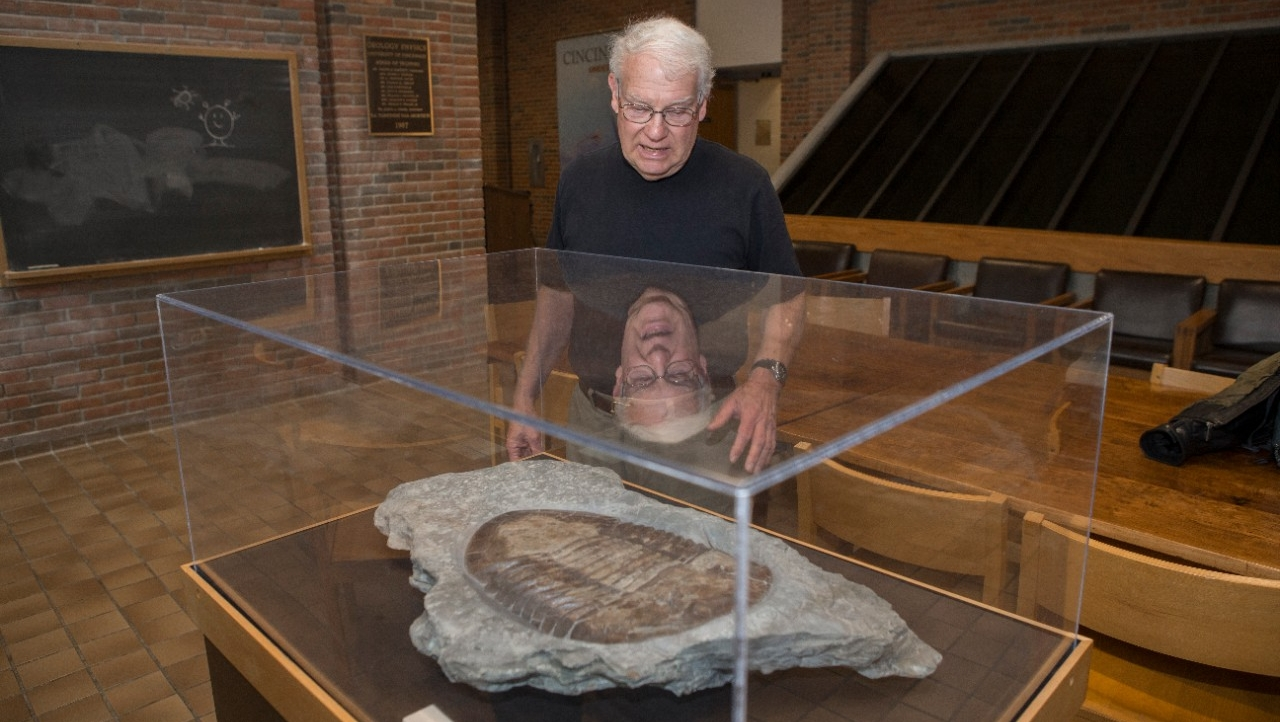 UC geology professor emeritus David Meyer stands in front of a trilobite on loan from the Cincinnati Natural History Museum.