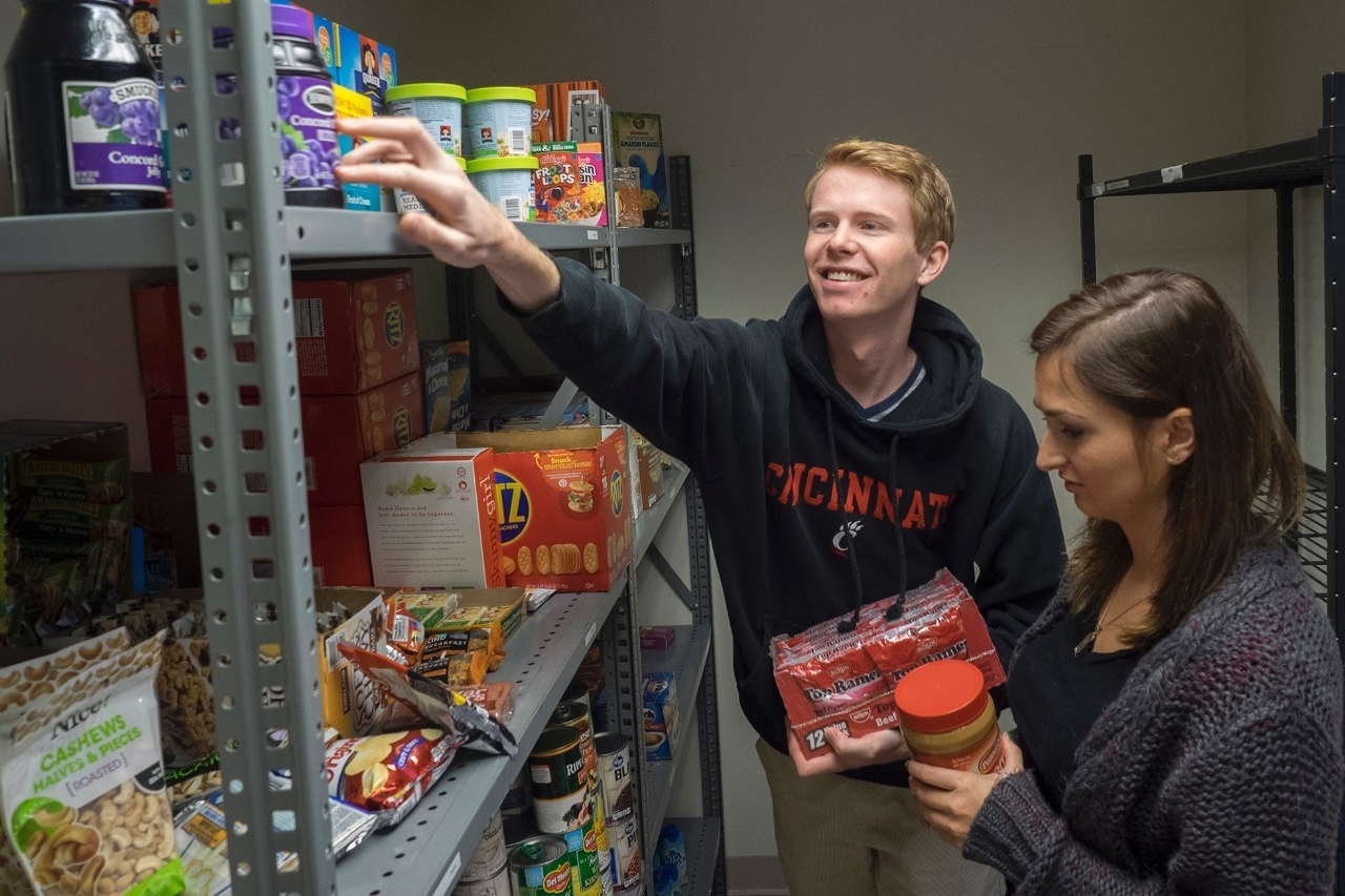 UC Food Pantry students stand near shelves of free food.