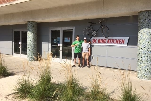Student bike mechanics stand outside UC's Bike Kitchen fix-it shop.
