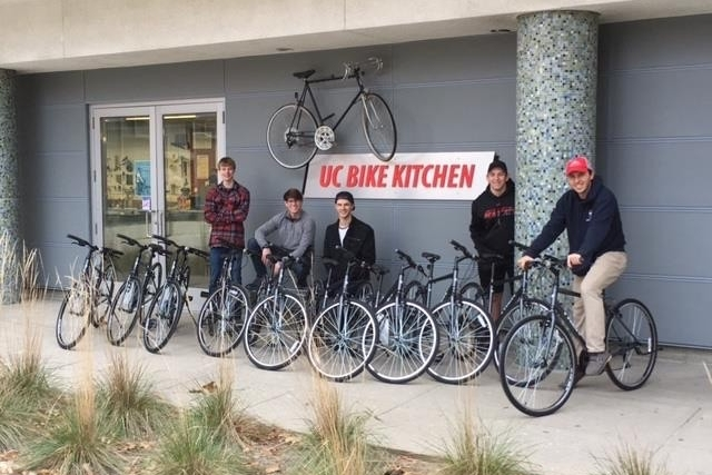 UC students stand outside UC's Bike Share and Bike Kitchen with their bikes.