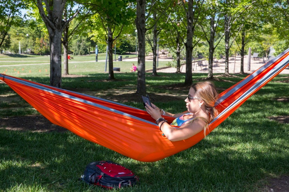 UC student sits on campus in an Eno hammock between trees.