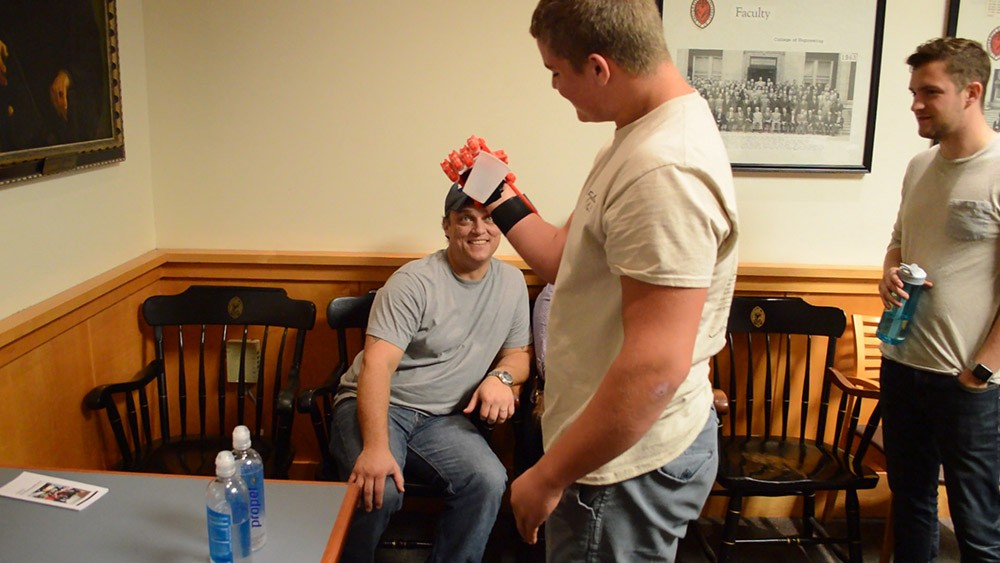 Prosthetic recipient T.J. McGinnis picks up a drinking cup, utilizing his device created by EnableUC.