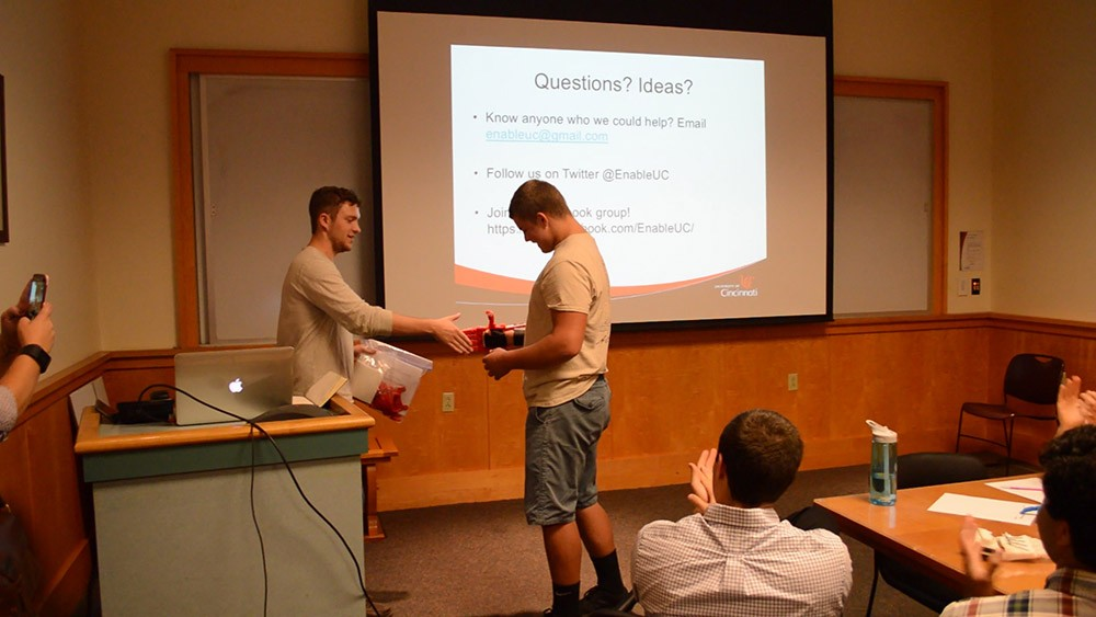 Prosthetic recipient T.J. McGinnis shakes Jacob Knorr's hand, utilizing his device created by EnableUC.