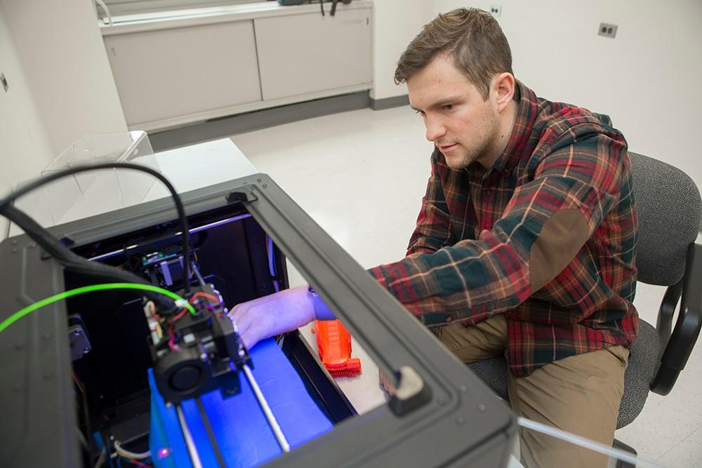 Jacob Knorr reaches into EnableUC's 3-D printer.