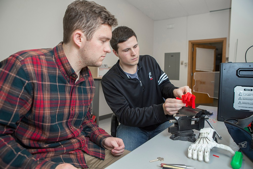Jacob Knorr and Nick Bailey work on a 3-D printed prosthetic hand.