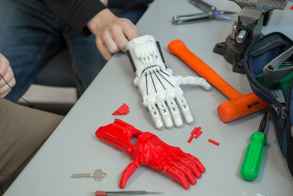 A completed white prosthetic hand lays next to an in-progress red prosthetic.