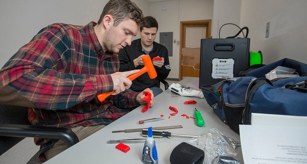 EnableUC president Jacob Knorr and co-vice president Nick Bailey work on a 3-D printed prosthetic hand on a desk covered in tools.