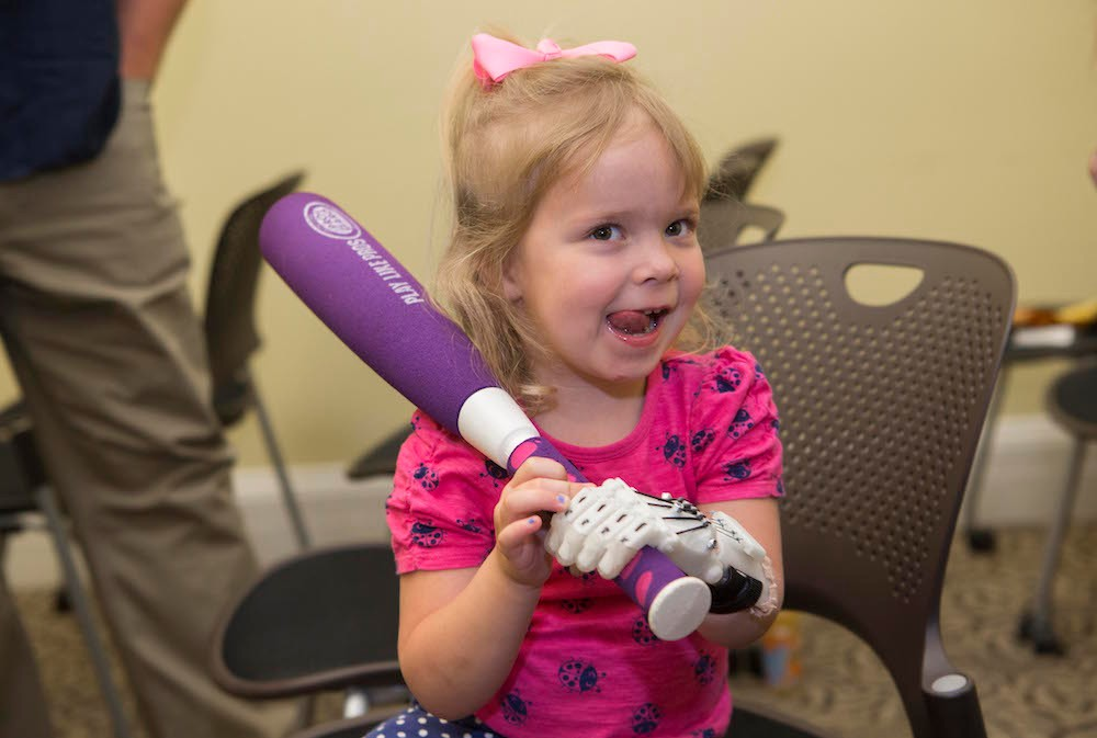Ella Morton, 3, shows off her new prosthetic hand at UC Board of Trustees meeting.