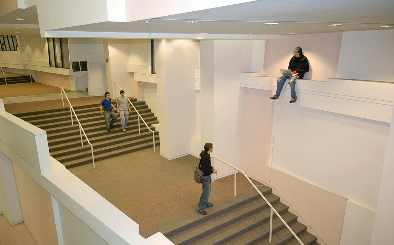 A life-sized sculpture of a student is perched on a ledge high above a stairway.