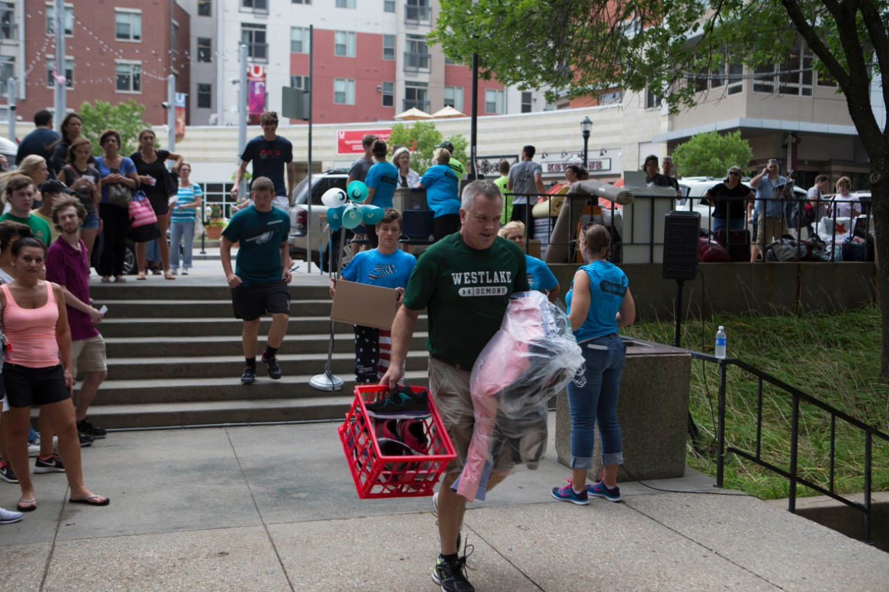 A man carries a plastic tub as students move into campus dorms.